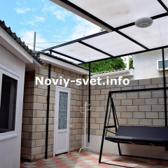 Двор частично накрыт крышей. Дверь слева - на   кухню.  Дверь справа - в санузел. По центру проход к калитке.