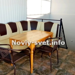 мягкий уголок. стол и стулья на террасе, расположенной над кухней